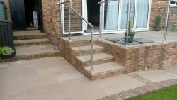 Patio in Autumn brown sandstone with glass surround